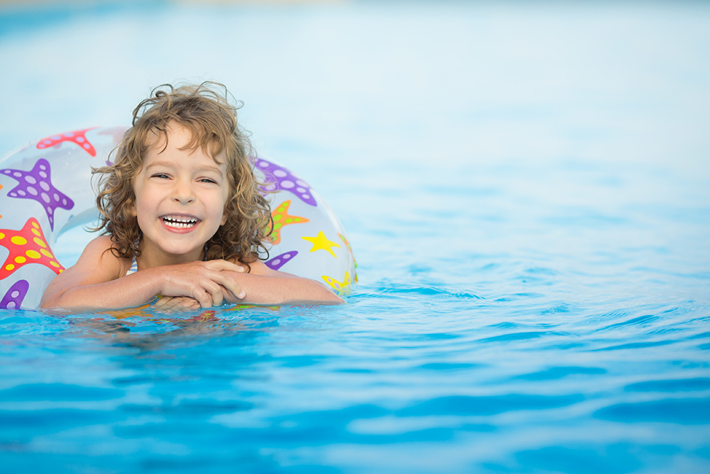 Happy child playing in swimming pool.